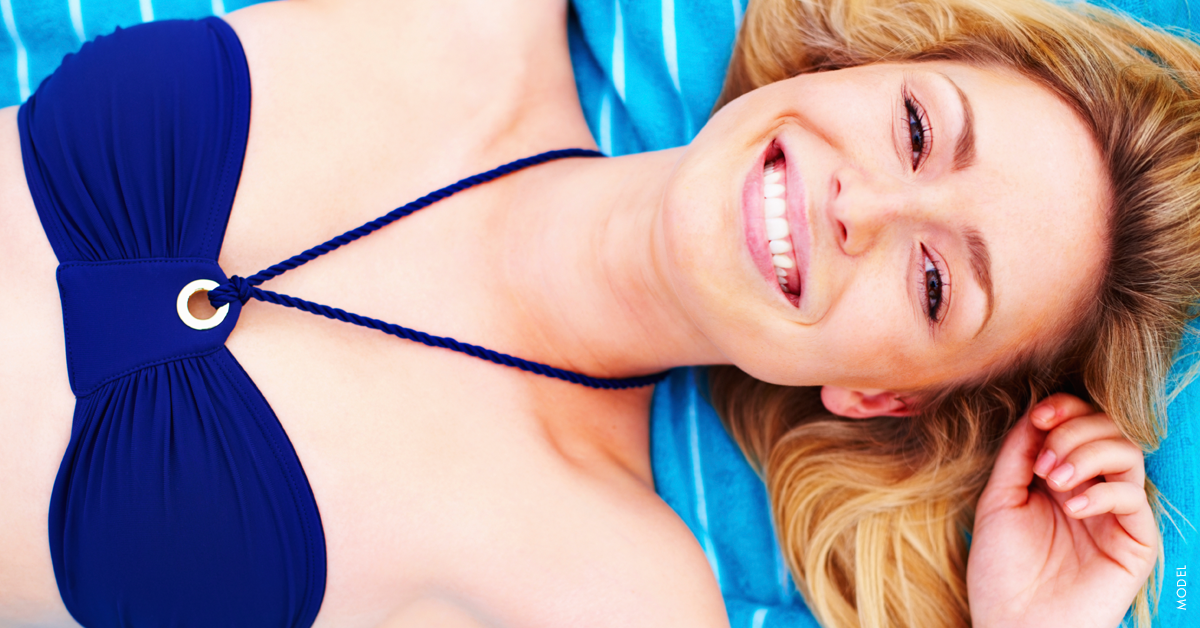 Young woman in a blue swimsuit considering breast augmentation during the summer