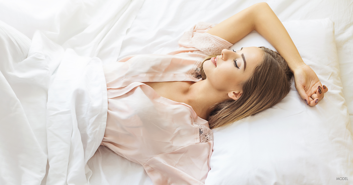 Young woman sleeping after her breast augmentation procedure.