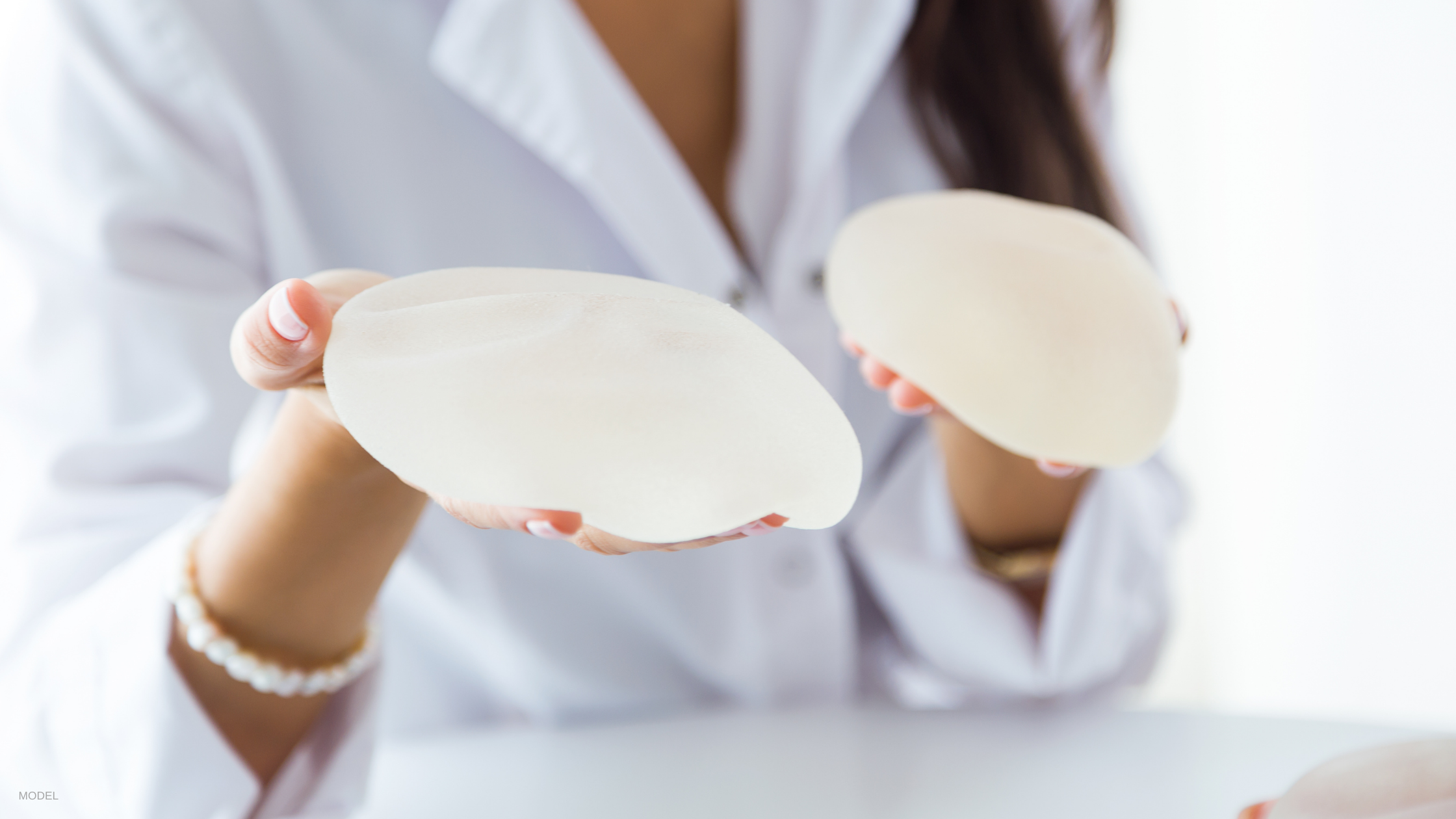 Woman holding breast implants